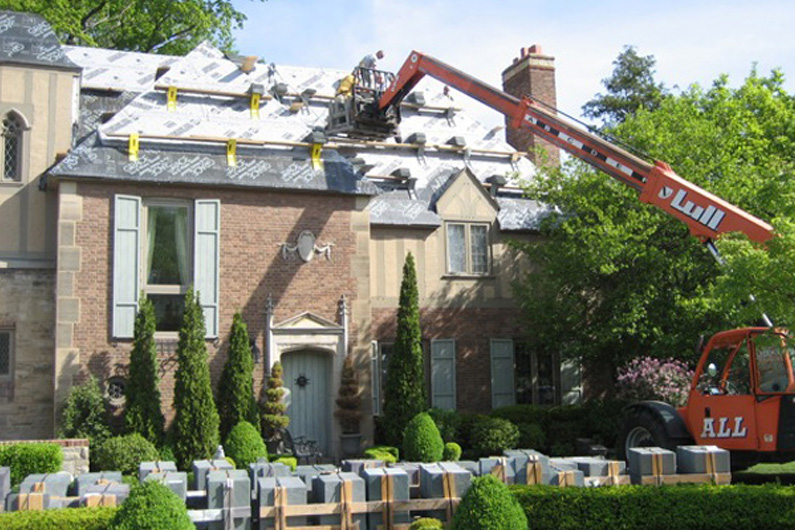 The Greenstone slate is being lifted to the roof during installation.