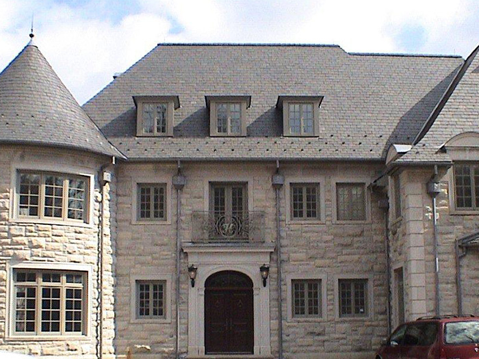 Elegant gray stone residence with Vermont Clear Black slate roof